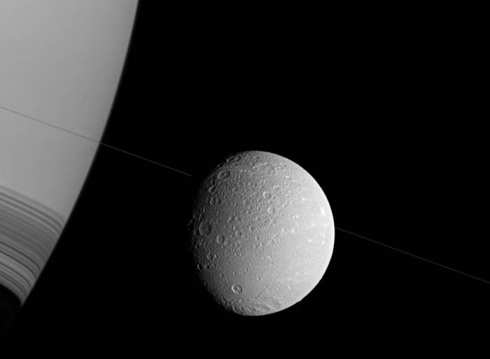 В центре изображения Диона. Правую часть занимает гигантский бок Сатурна. Фото NASA/JPL-Caltech/Space Science Institute